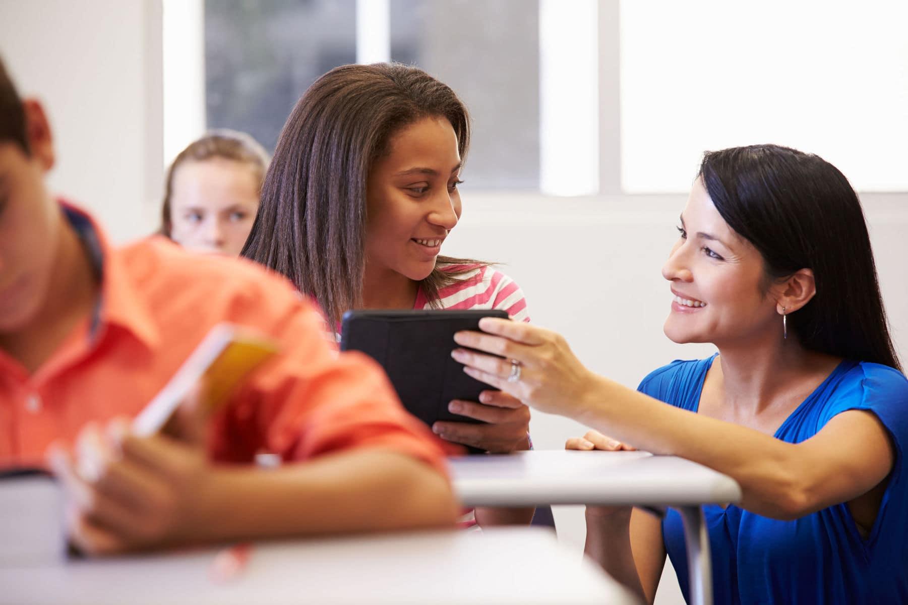 Girl talking to school teacher