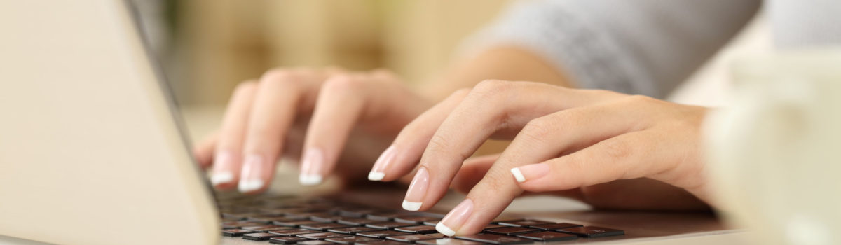 Office worker typing up job description as her office prepare to recruit