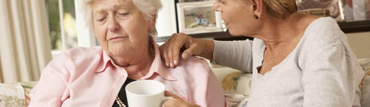 An elderly lady being comforted
