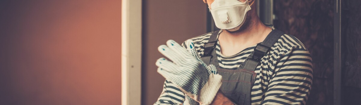 Builder putting on his protective wear before starting job