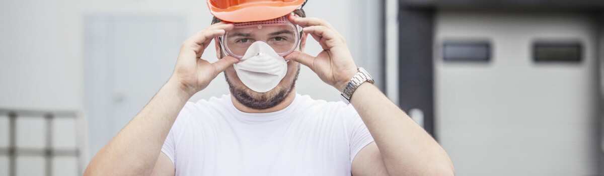 Worker ensuring his eye protection is fitted correctly to prevent accident