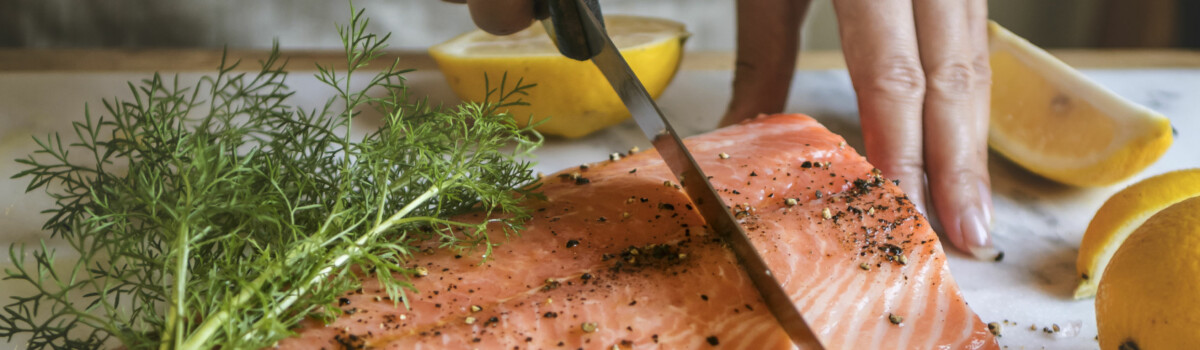 Raw fish being cut up before cooked to reduce the risk of salmonella poisoning