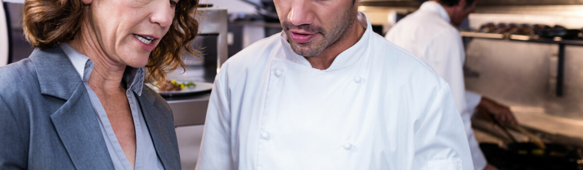 Chef and front of house manager stood discussing any possible allergens in the food listed on the menu