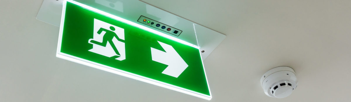 Fire exit sign illuminated in school corridor