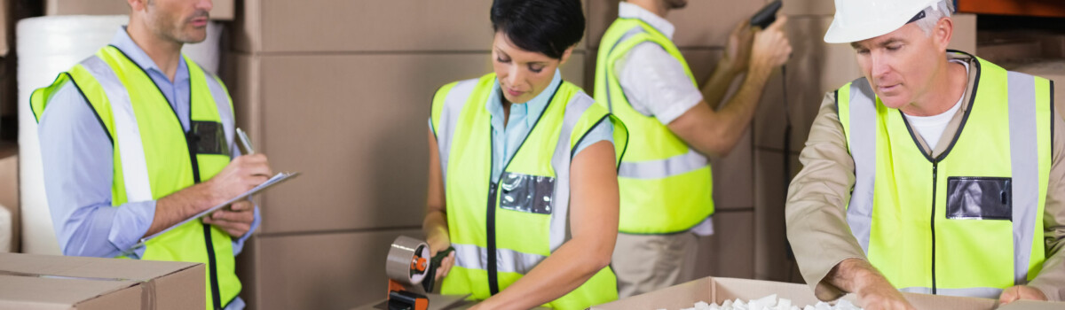 Motivated warehouse workers hard at work after motivating talk