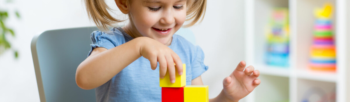 Little girl learning resilience being independent using building blocks