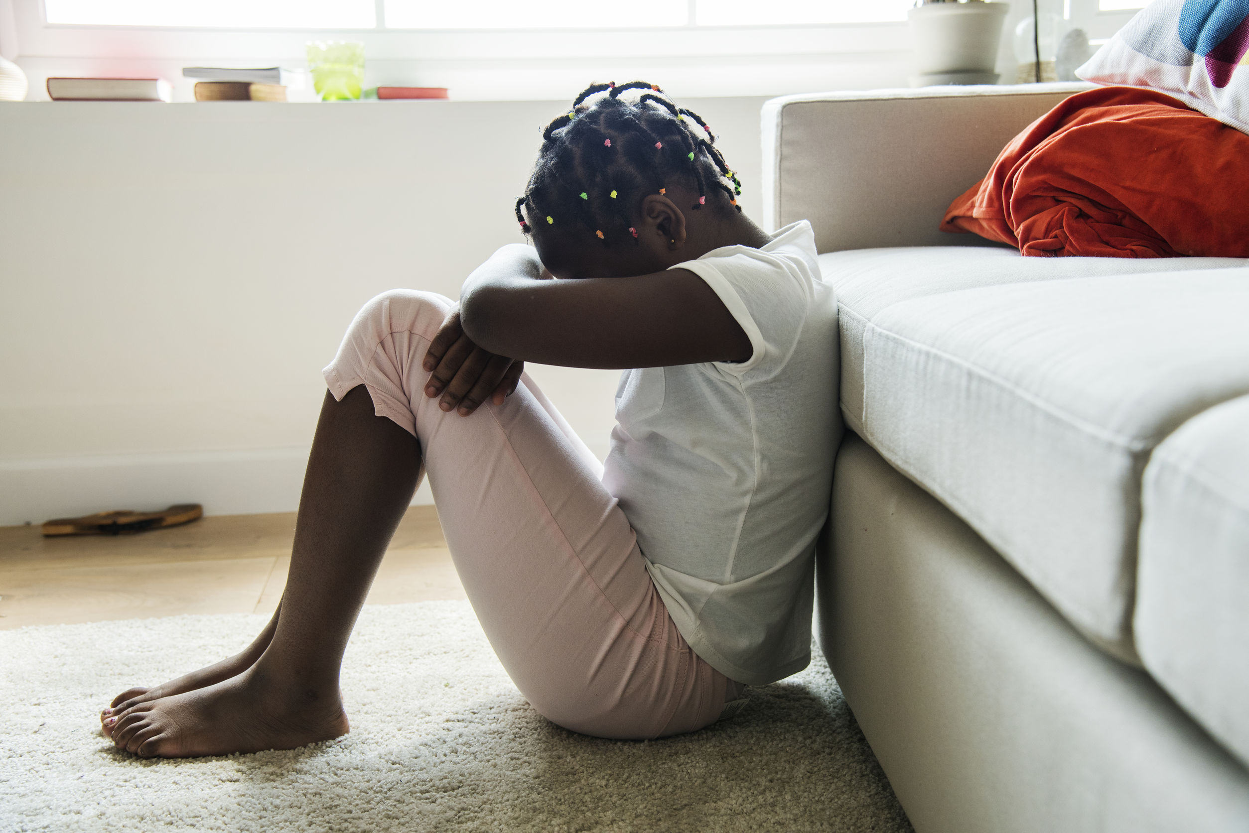 Upset young girl sat on the floor with low self-esteem after having female circumcision carried out when she was younger