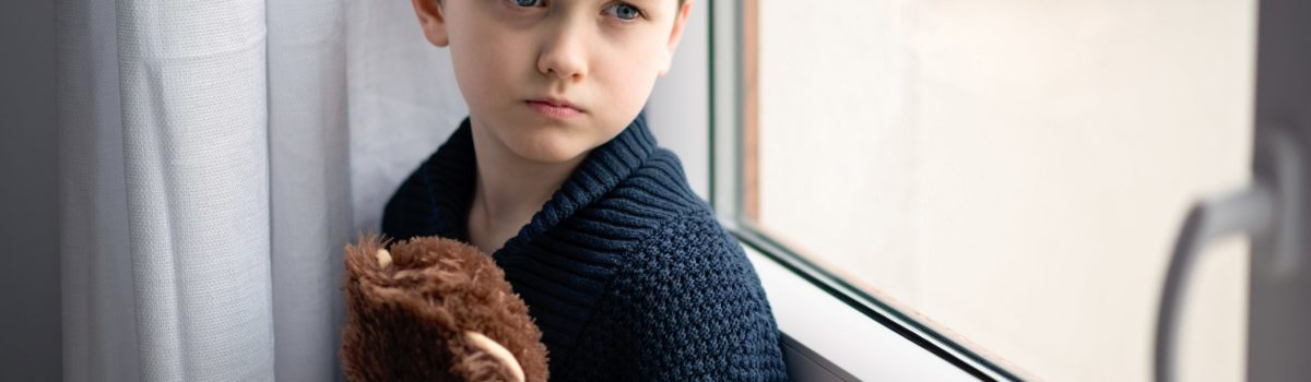 Vulnerable young boy sat upset with his teddy bear