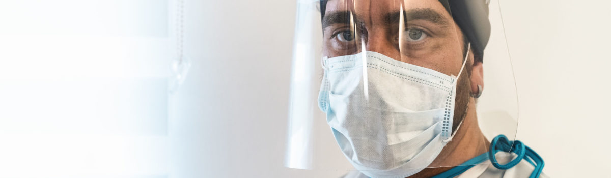 Doctor wearing face PPE before entering hospital room