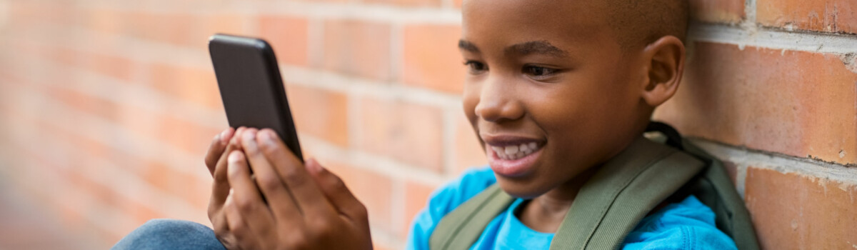 Child Playing On Phone As He Plays Online Safely