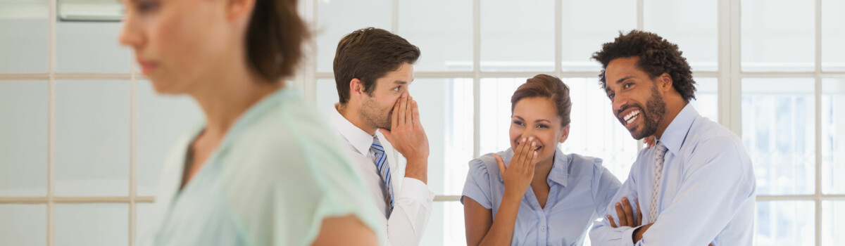 Colleagues gossiping about another worker in front of her