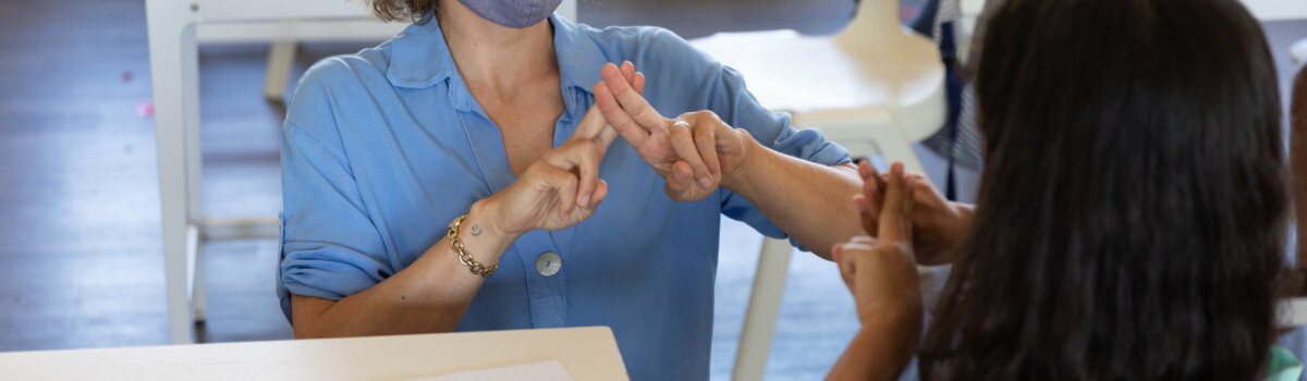Teacher using sign language as a way of inclusive practise with her student