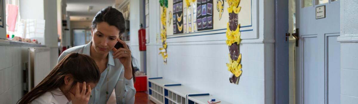 Upset child is with her teacher